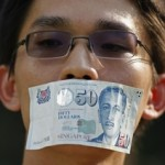 A man covers his mouth during a protest against new media regulations, in Singapore