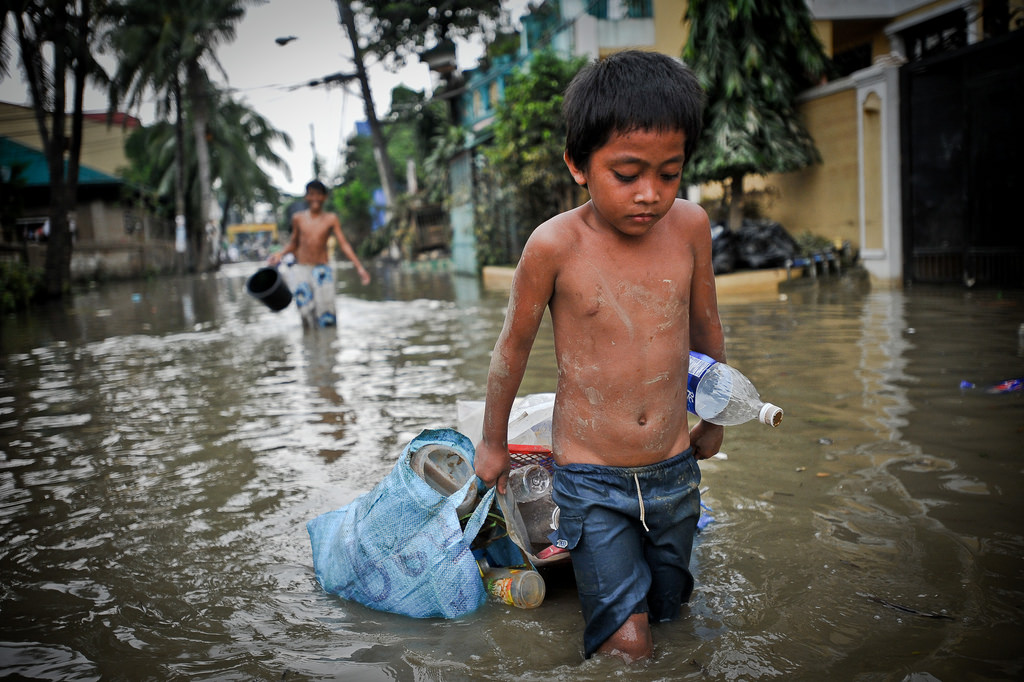 A young boy carries his belongings through flood water