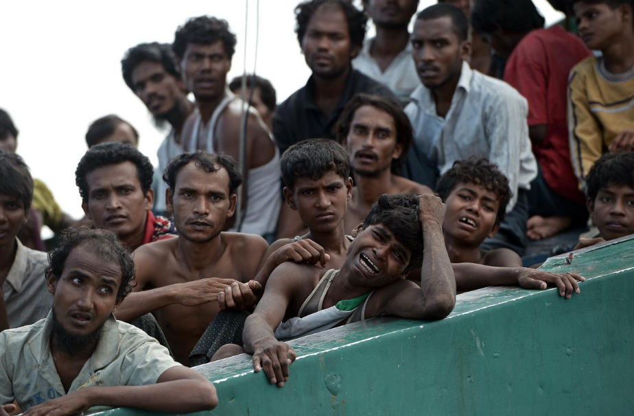 A Rohingya migrant cries as he sits with others in a boat