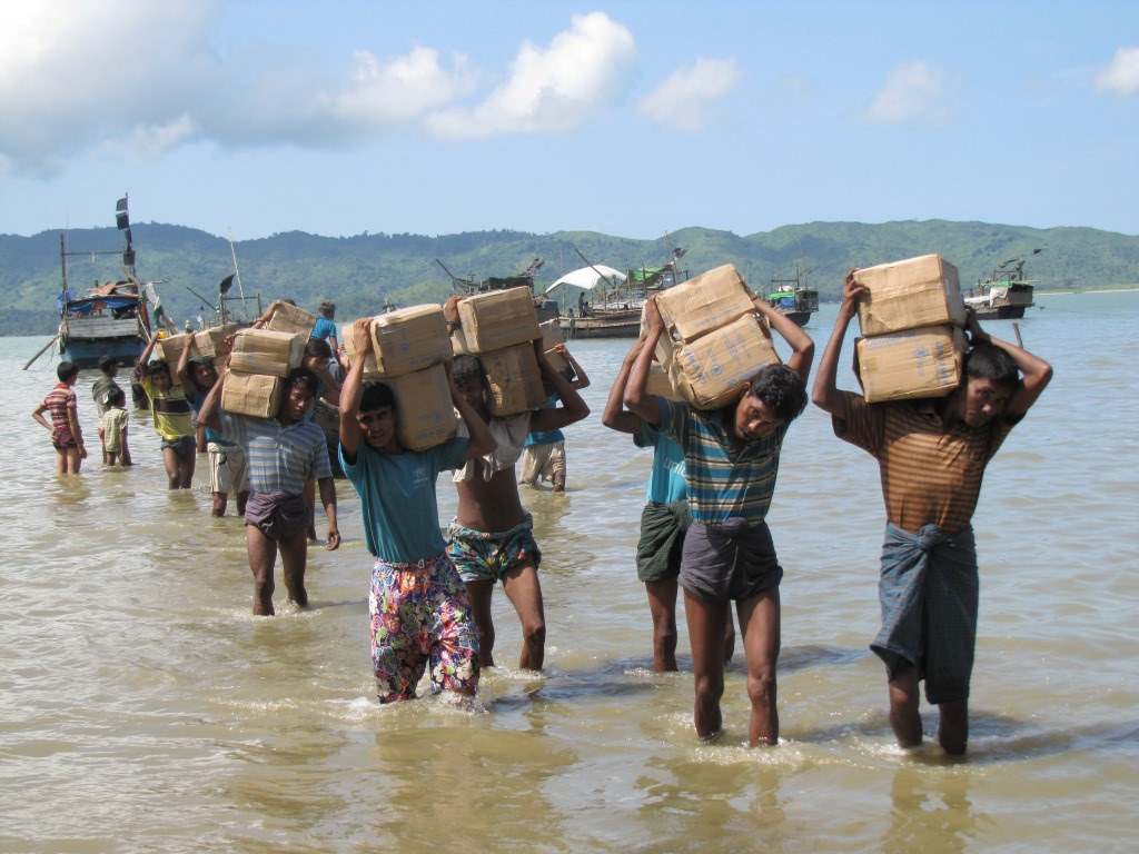 Rohingya Refugees carry boxes of Humanitarian Aid
